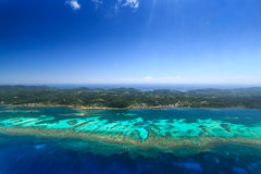 Aerial image defines coral reef off coast of tropical island Royalty Free Stock Photos