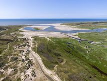 Aerial image of dutch national park slufter with curving rivers in grass land towards the north sea on the island of Texel. Aerial shot by drone of sunset over stock photo