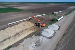 Excavator working in field for district heating. Aerial image of excavator digging pit for district heating line in field royalty free stock image