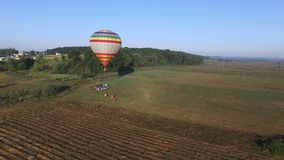 Aerial image of a hot air balloon flying up. Aerial image of a hot air balloon flying up on summer morning in the field stock footage