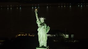 Aerial photo of the Statue of LIberty telephoto lens shot. Aerial image of the Statue of LIberty at night with New York City in the background royalty free stock photo
