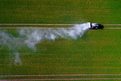 Aerial image of tractor spraying pesticides on green oat field shoot from drone royalty free stock photo