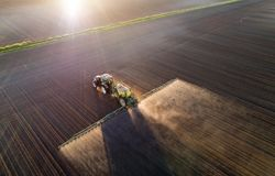 Tractor spraying soil in field. Aerial image of tractor spraying soil and young crop in springtime in field royalty free stock images
