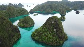 Aerial of Islands and Calm Lagoon in Raja Ampat. Rugged limestone islands, surrounded by coral reefs, are found in an idyllic, tropical lagoon in Wayag, Raja stock video