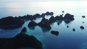 Aerial of Islands and Calm Lagoon in Raja Ampat. Rugged limestone islands, surrounded by coral reefs, are found in an idyllic, tropical lagoon in Wayag, Raja stock video footage