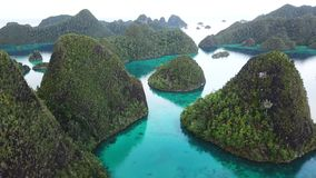 Aerial of Islands and Calm Lagoon in Wayag, Raja Ampat. Rugged limestone islands, surrounded by coral reefs, are found in an idyllic, tropical lagoon in Wayag stock video