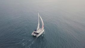 Aerial 4K footage of luxury catamaran yacht with white and red sail in blue seas. Aerial 4K drone footage of a luxury catamaran yacht with white and red sails stock footage