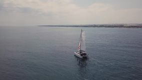 Aerial 4K footage of luxury catamaran yacht with white and red sail in blue seas. Aerial 4K drone footage of a luxury catamaran yacht with white and red sails stock video footage