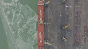 Aerial 4k UHD footage Cargo freight ship with working crane bridge in shipyard for Logistic Import Export background. Top view stock video footage