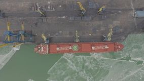 Aerial 4k UHD footage Cargo freight ship with working crane bridge in shipyard for Logistic Import Export background. Top view stock video