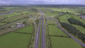 Aerial 4k video of a busy Irish motorway with fly over bridge and roundabouts. stock video footage