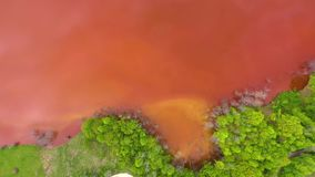 Aerial 4k drone view of colorful red copper mining waste water in contrast with fresh green forest stock video footage
