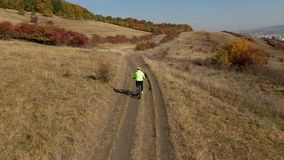 Aerial 4k view of a cyclist riding bike in the outdoors by drone stock footage