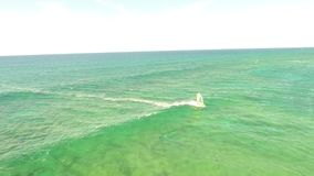 Aerial 4k view on professional windsurfer gliding in calm turquoise blue ocean wave water seascape, extreme summer sport. Aerial view on professional windsurfer stock video