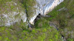 Aerial 4k view of a waterfall and big cave entrance by drone stock video