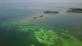 Aerial of Lagoon and Tropical Island Resort in Belize. Aerial view of a gorgeous resort on a small, remote island in Turneffe Atoll, Belize. The area supports a stock video footage