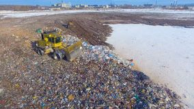 Aerial. Landfill truck moves with a raised blade at a city landfill. Waste, garbage, dump, rubbish 4K. A landfill compactor with a raised bucket drives away to stock video