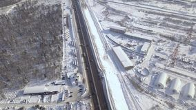 Aerial landscape car and cargo truck moving on winter highway through snowy forest. Car traffic on winter road drone. View. Car driving on snow highway on stock footage