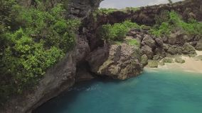 Aerial landscape cliff on rocky sea shore. Beautiful blue sea waves splashing by rocky cliff on coast. Turquoise ocean. Water and rocky island drone view. Bali stock footage