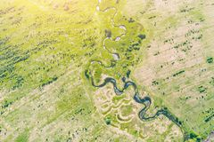 Aerial landscape countryside of winding small river, stream in green field, top view meadow.  stock photo