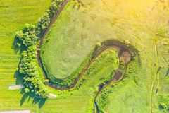 Aerial landscape countryside of winding small river, stream in green field, top view sunset meadow.  stock photos