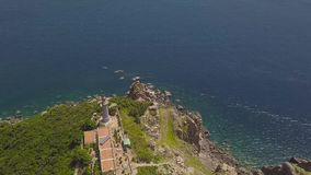 Aerial landscape light house on mountain cliff on sea shore and blue water. Drone view lighthouse on tall mountain and stock video