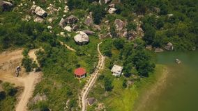 Aerial landscape mountain road on background green lake and big stones. Road along lake shore and green rocky hills view. From flying drone stock footage