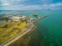 Aerial landscape of parking lot and industrial wharfs near ocean coastline at Williamstown suburb with Melbourne CBD skyline in th. E distance Royalty Free Stock Photos