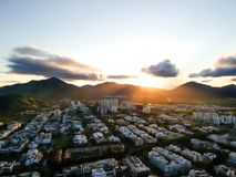 Aerial landscape photo of Recreio dos Bandeirantes beach during sunset, with the sun dipping behind the mountains and stock image