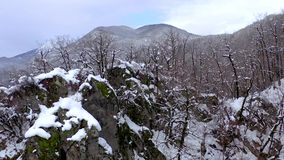 Aerial landscape view of Caucasus Mountains in Gorky Gorod, Sochi, Russia. Trees and rocks covered with snow. Aerial landscape view of Caucasus Mountains in stock video footage