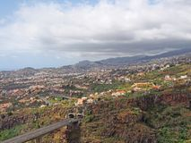Aerial landscape view of the motorway bridge in funchal entering a tunnel in the valley with buildings and streets of the city. An aerial landscape view of the stock photography