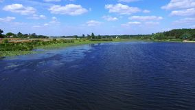 Aerial landscape village on river shore. Fisherman catching fish on fishing boat. Drone view summer fishing in river at countryside stock video footage