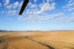 Aerial landscape of dunes and surrounding Sossusvlei Namibia. Aerial landscape, wide flat  area stretching to horizon with helicopter rotor blade  from tourist Royalty Free Stock Photography