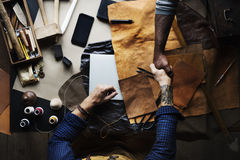 Aerial of leather craftsmen shaking hands together Stock Image