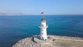 Aerial of lighthouse near the blue ocean. Art. White beautiful beacon with walking tourists and clear sky with the. Aerial of lighthouse near the blue ocean stock video footage