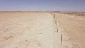 Aerial of a long fence running through a desert landscape