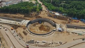 Aerial long shot of construction of traffic circle in Samara city, summer, modern buildings. Cars moving around stock video footage