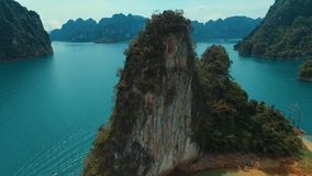 Aerial: The long tail boat and a lonley rock on the lake. stock video