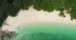 Aerial: A loving couple lies alone on the white sand deserted beach. stock video footage