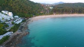 Aerial: Luxury hotel at Nai Harn beach in sunset time look around. HD birds eye view. Blue water with rocks. stock video
