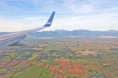 Aerial Mallorquin landscape. MALLORCA, BALEARIC ISLANDS, SPAIN - DECEMBER 25, 2016: Scandinavian Airlines wing over green Mallorquin landscape on December 25 Stock Images