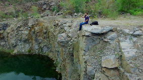 Aerial: Man takes photos on peak of rock stock video