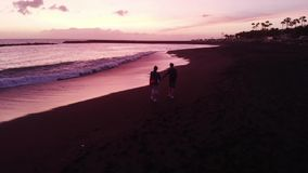 Aerial. A man and a woman run along a black volcanic beach on a pink beautiful sunset. Tenerife, Spain. 2k stock footage