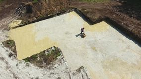 Aerial of man working with plate compactor in foundation pit of new house stock video footage