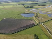 Aerial of meadowland with curving dike cycle lane and water storage on the dutch island of Texel. Aerial by drone of meadowland with curving dike cycle lane and stock photos