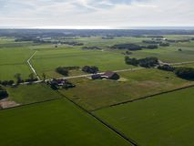 Aerial of meadowland and farms on the dutch island of Texel with the sea visible on the horizon. Aerial of meadowland by drone and farms on the dutch island of royalty free stock image