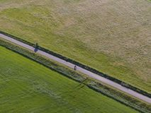 Aerial of meadowland separated by straight bicycle lane with cyclist on the dutch island of Texel. Aerial made by drone of meadowland separated by straight royalty free stock photos