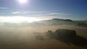 Aerial misty morning landscape, Tree in sunbeam mist. Aerial misty morning landscape with sun beam over tree in countryside stock video footage