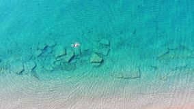 Aerial morning view of man swimmning in clear water. Summer time morning. stock video