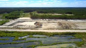 Aerial motion over lakes to sand quarry with excavator stock video